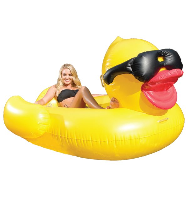 Woman lounging on a giant yellow duck with black sunglasses inflatable pool float against a white background